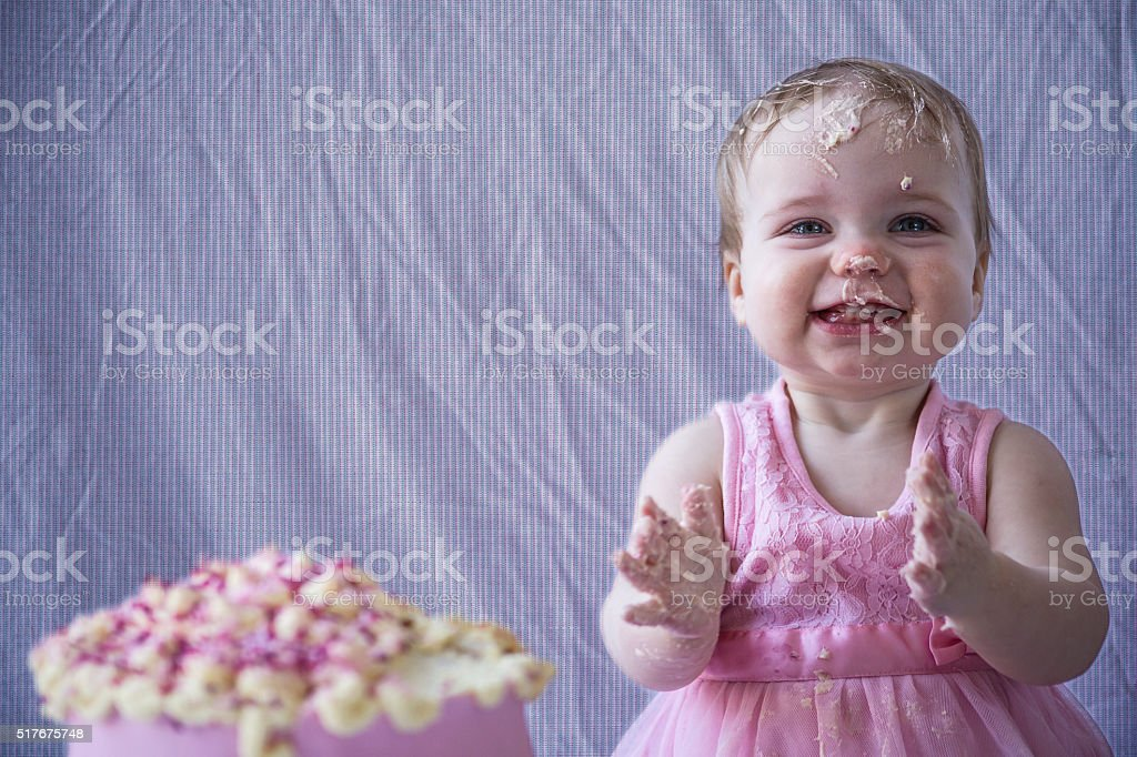 baby girl has fun with cake stock photo