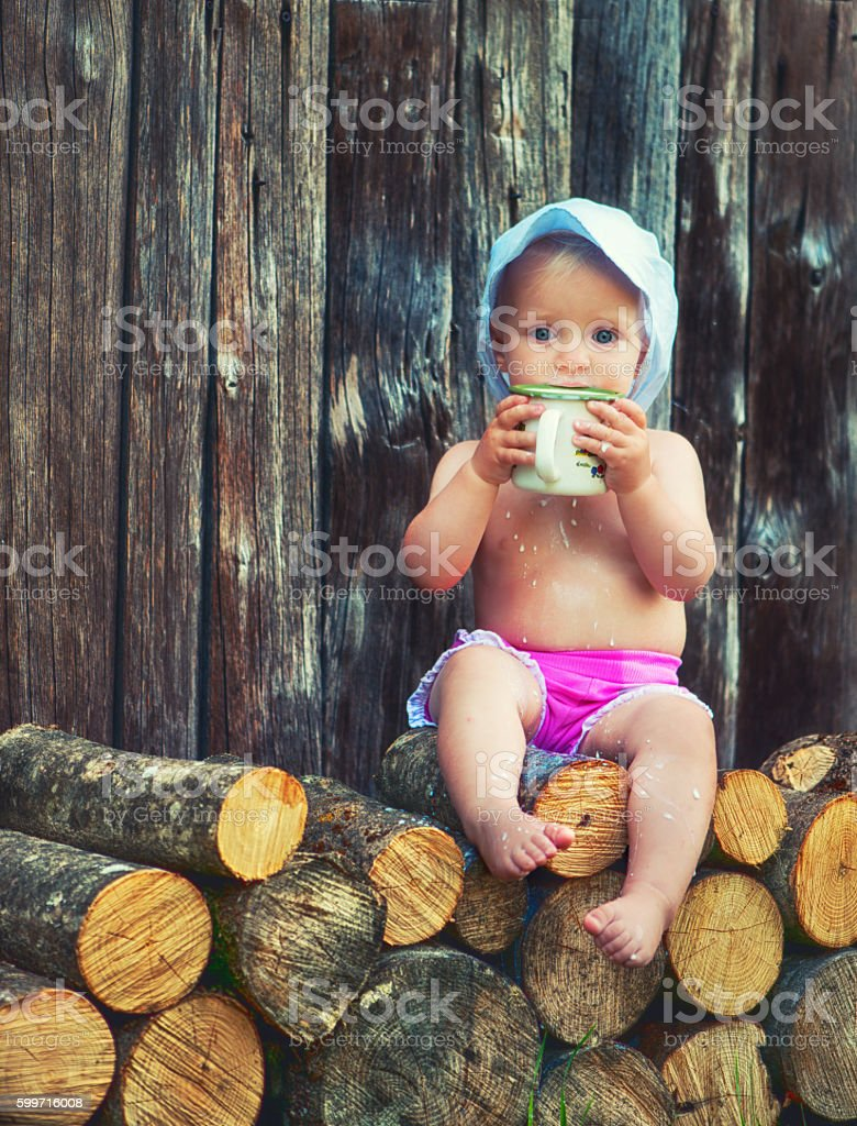 Baby girl holding a big metal cup stock photo