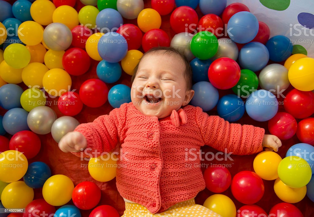 baby girl in a ball pit stock photo