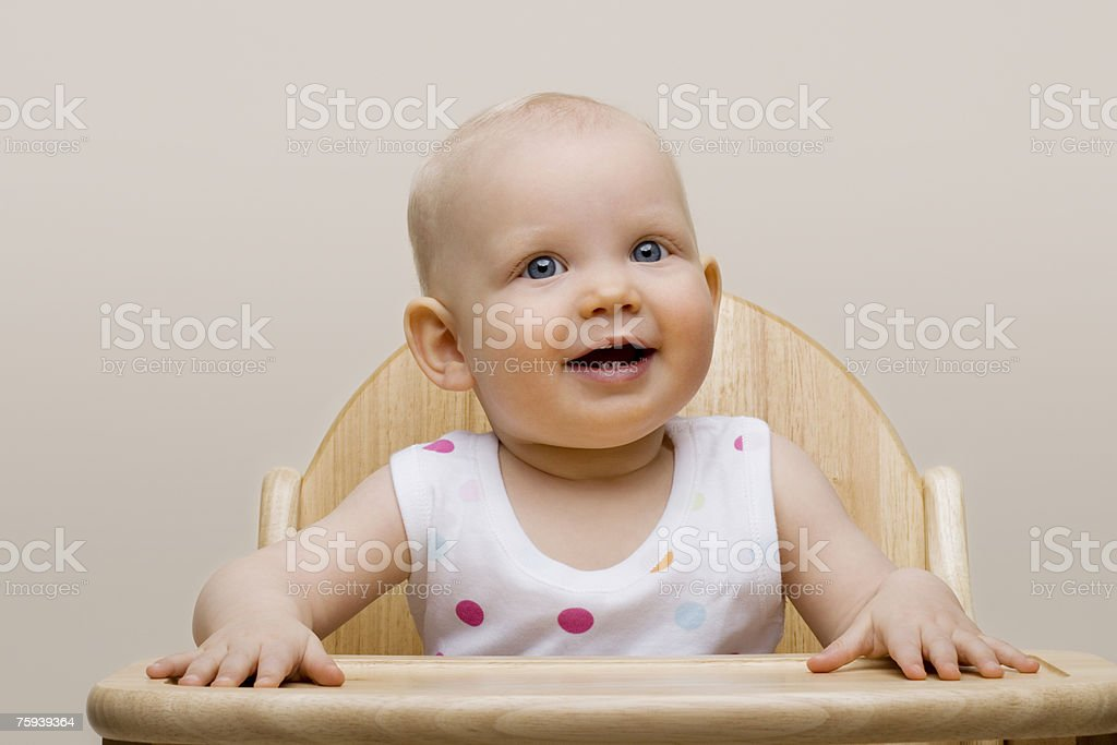 Baby girl in a high chair stock photo