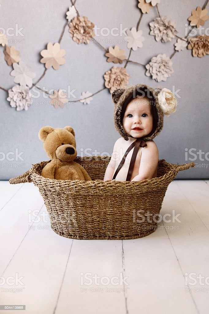 Baby Girl in Basket with Teddy Bear stock photo