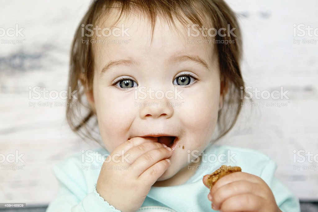 Baby girl in blue dress eating a cookie royalty-free stock photo