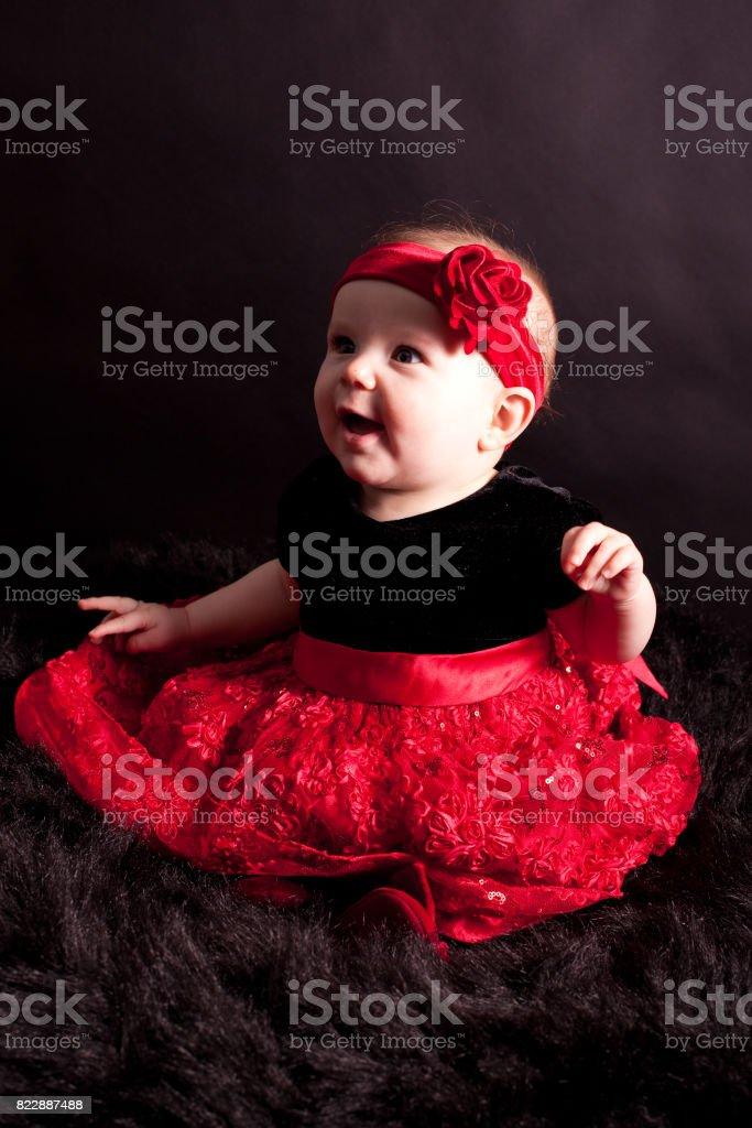 baby girl in full red skirt stock photo
