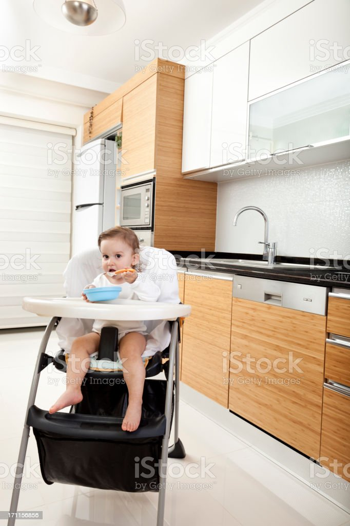 Baby girl (12-18 months )  in high chair eating from bowl stock photo