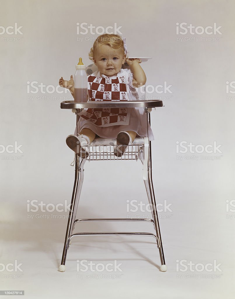 Baby girl in high chair holding plate, portrait stock photo