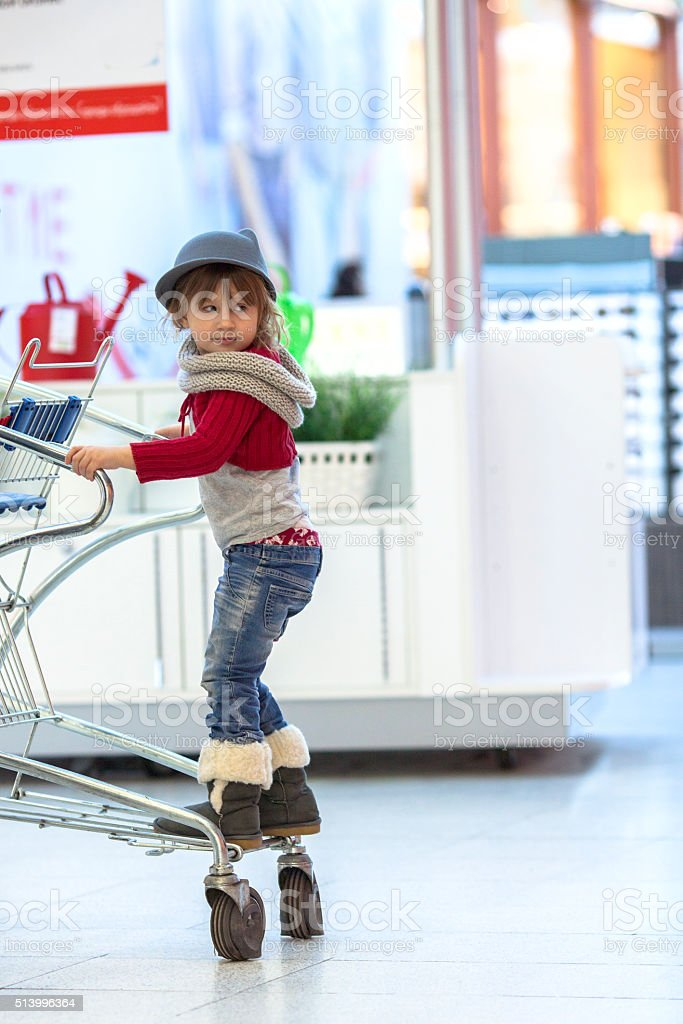 baby girl in jeans, hat fedora  walk the mall stock photo