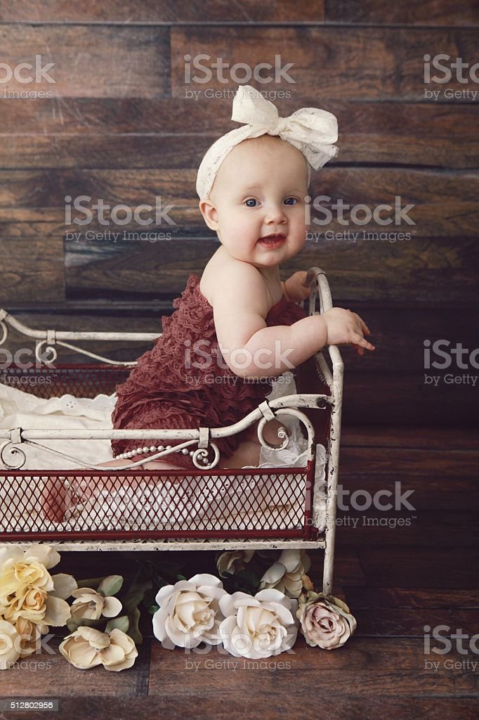 Baby Girl in Little Vintage Bed stock photo