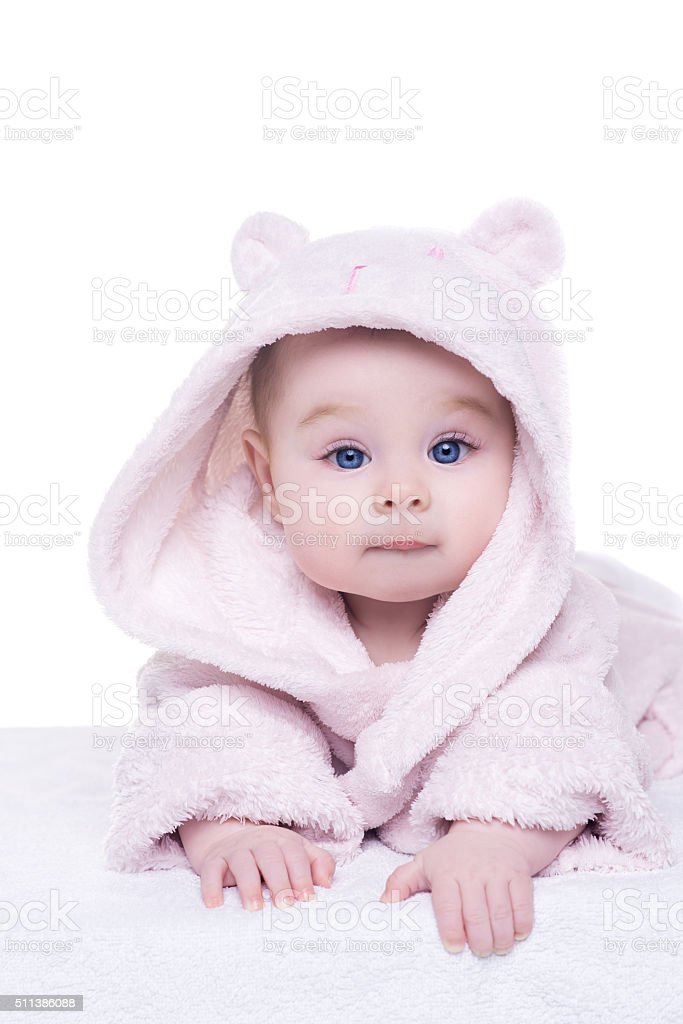 baby girl in pink bathrobe lying on her belly stock photo