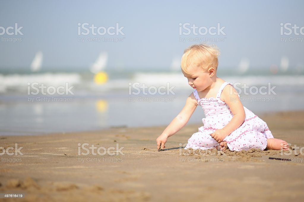 Baby girl in pretty dress playing on the beach royalty-free stock photo