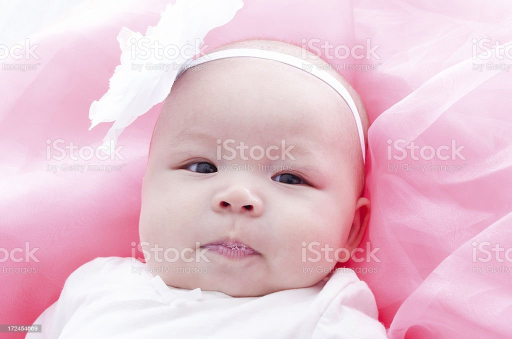 Baby girl in white on pink blowing bubbles. royalty-free stock photo