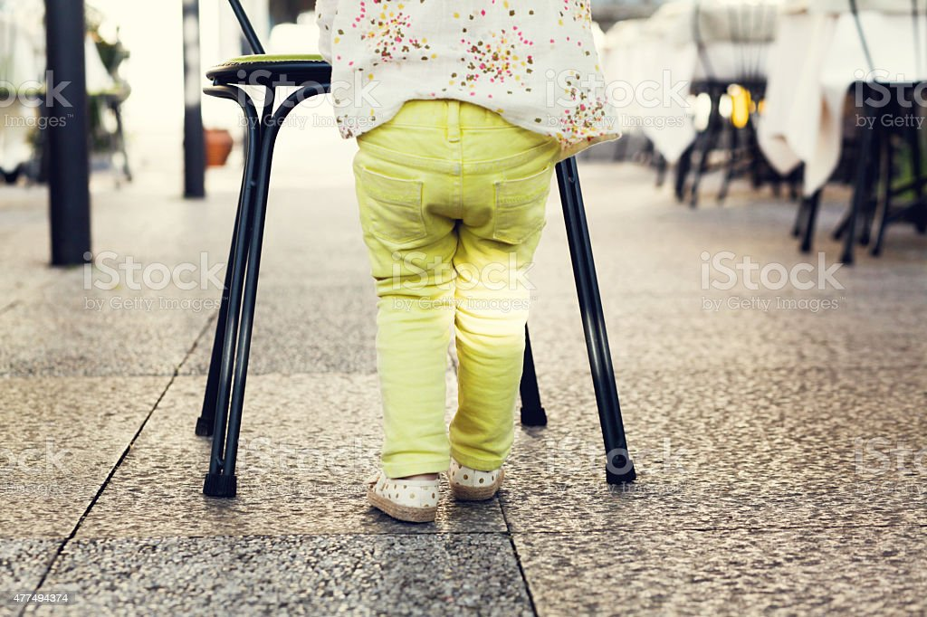 Baby girl in yellow pants stands in cafe stock photo