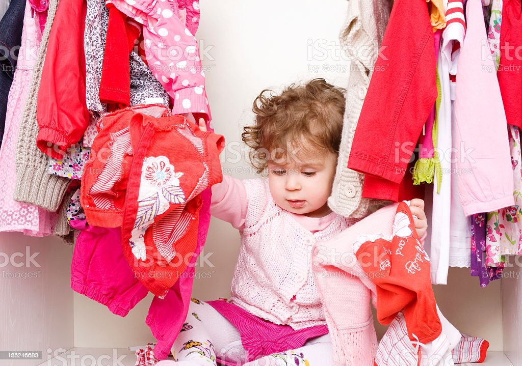 Baby girl inside a wardrobe with clothes royalty-free stock photo