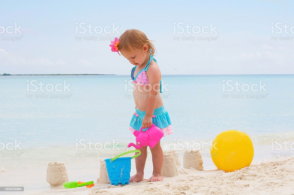 baby girl is playing on the beach stock photo