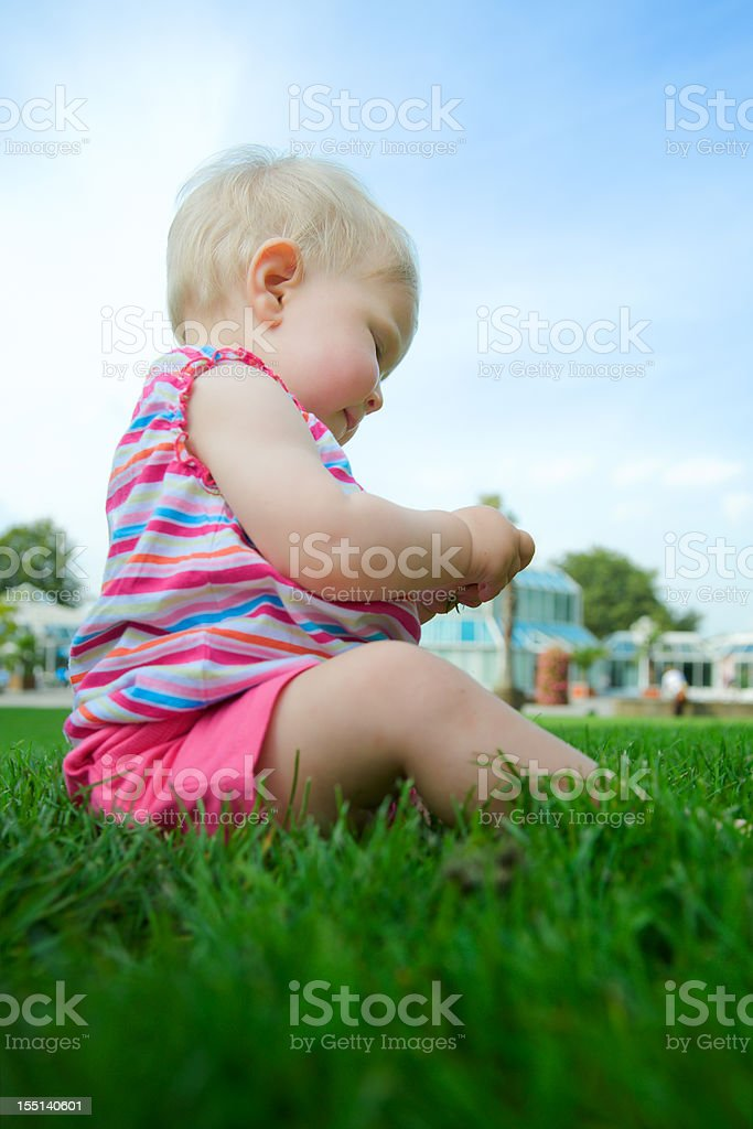 Baby Girl is sitting on a green meadow royalty-free stock photo