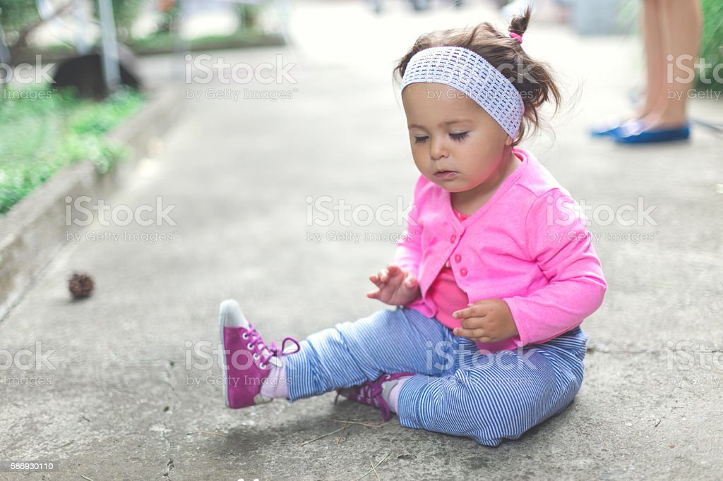 baby girl is sitting on the concrete floor stock photo