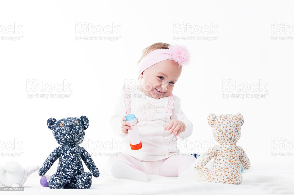 Baby girl laugh with teddy bear stock photo