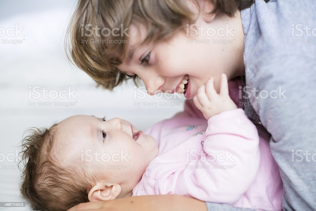 Baby girl laughing to her brother stock photo