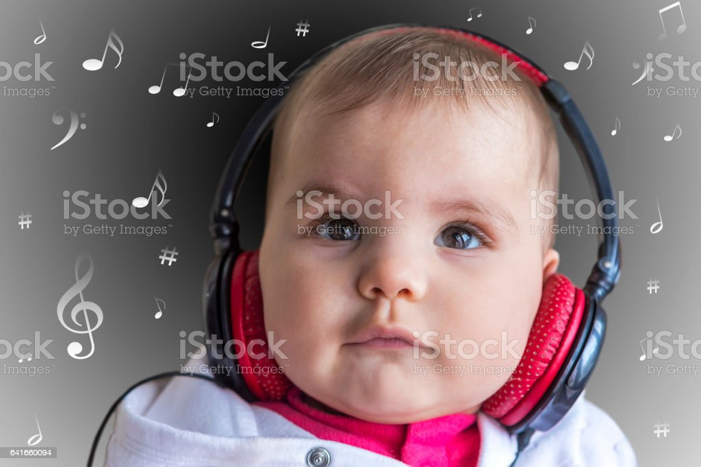 Baby girl listening to music stock photo