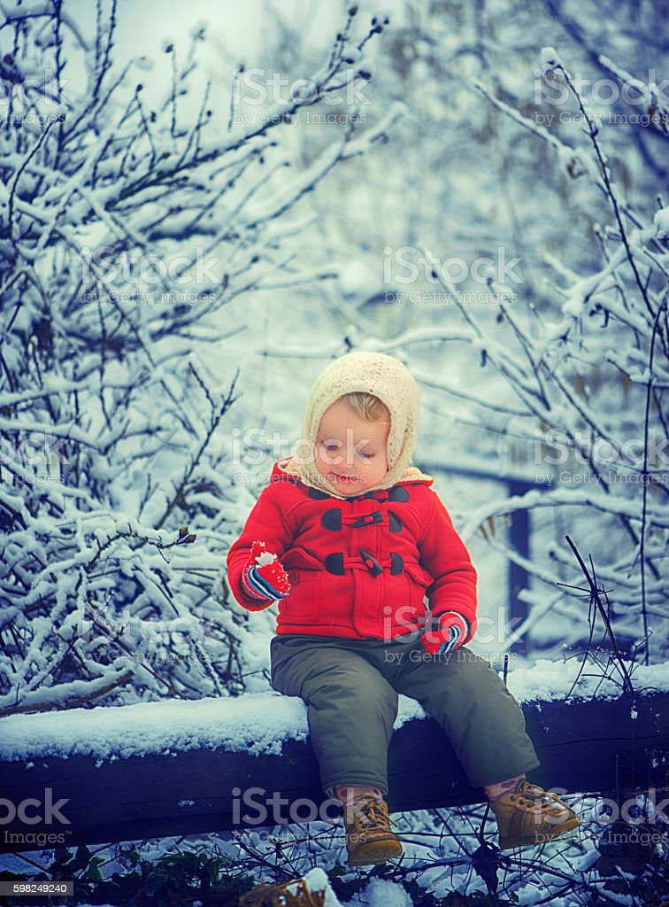 Baby Girl Looking at Snow in the Hand stock photo