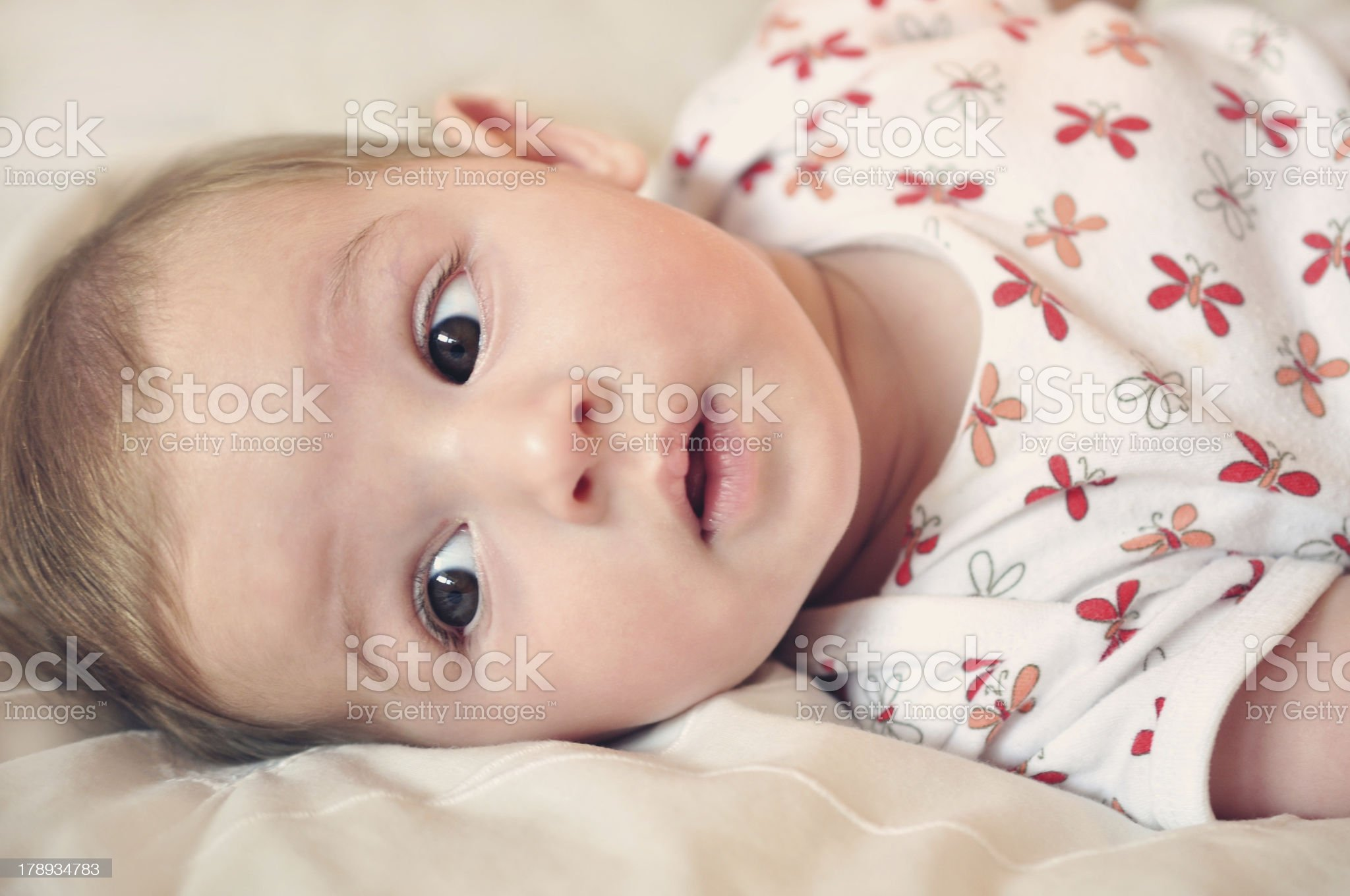 Baby Girl Looking Curious and Lying On a Bed royalty-free stock photo