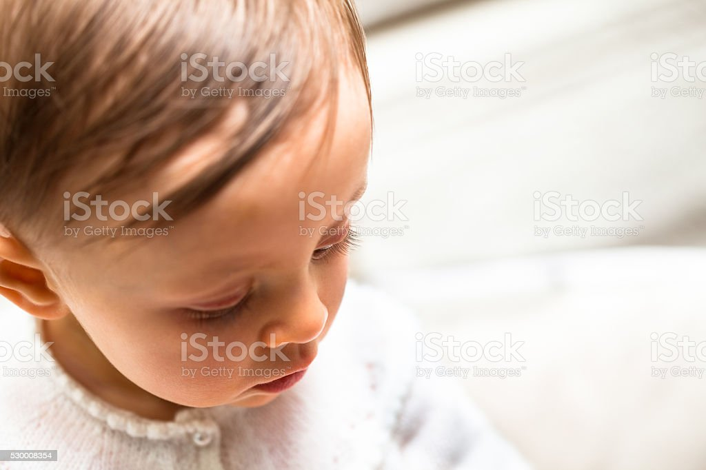 Baby girl looking downwards stock photo