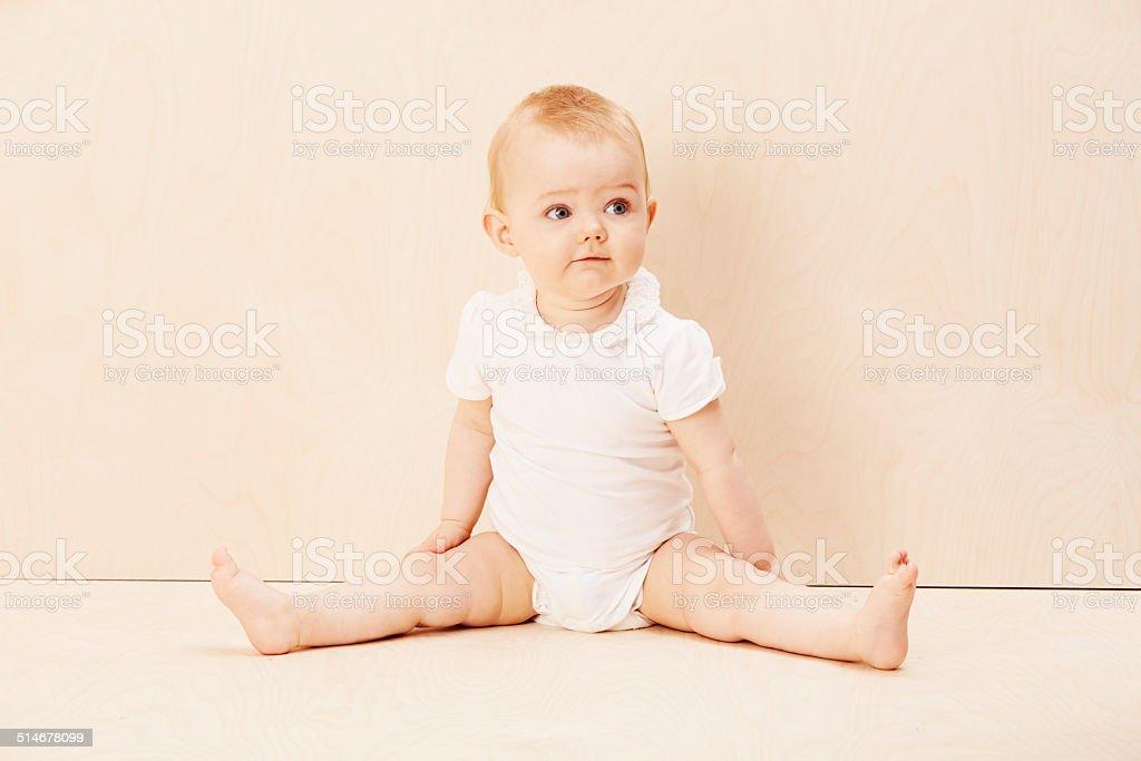 Baby girl looking up, studio shot stock photo