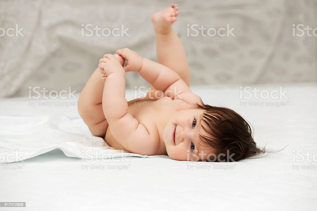 Baby girl lying on blanket indoors stock photo