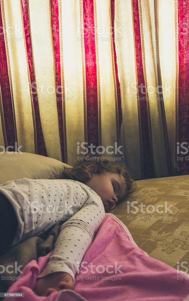 Baby girl lying on the bed sleeping stock photo