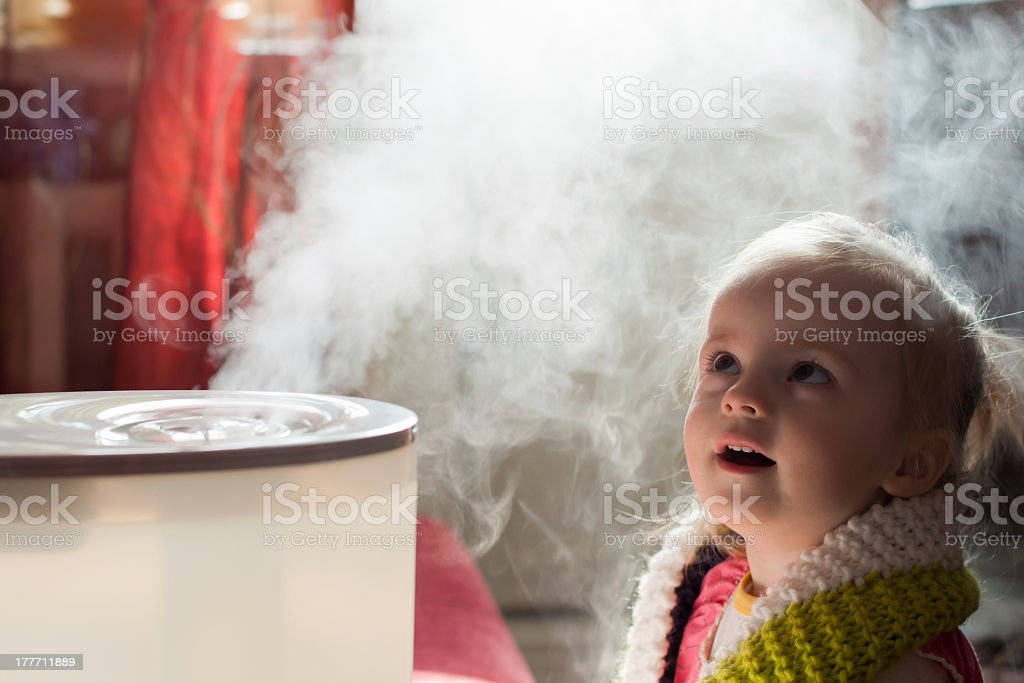 Baby girl mystifiied by a humidifier stock photo