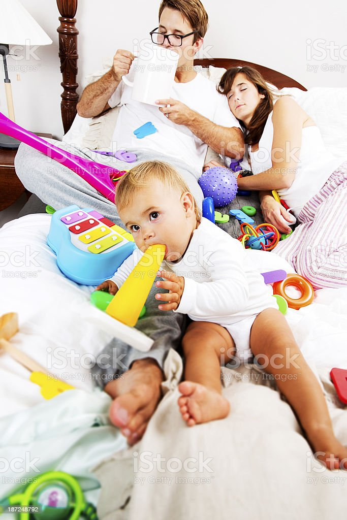 Baby Girl on a Messy Bed with her Parents stock photo