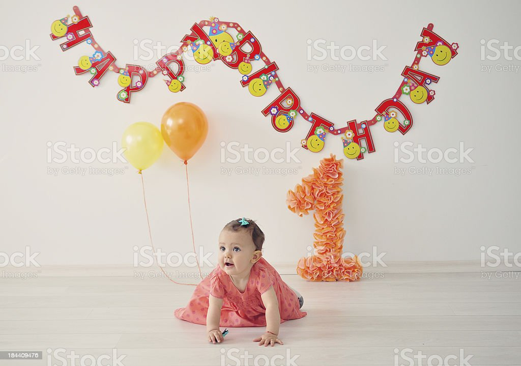 Baby girl on floor with happy birthday sign hung behind her  stock photo