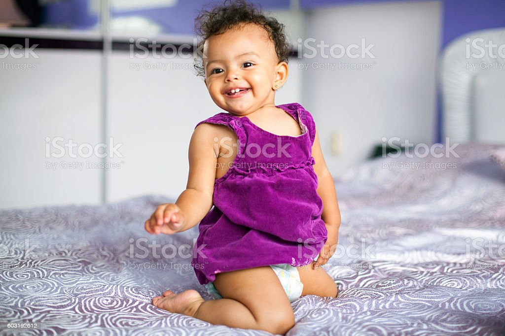 Baby girl on the bed in bedroom stock photo