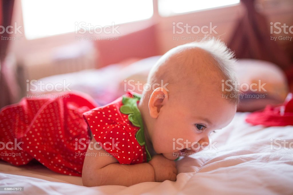 Baby girl on the bed,lying on front stock photo