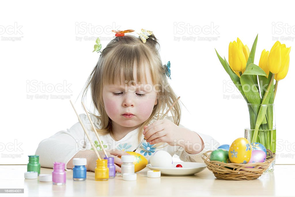 baby girl painting Easter eggs isolated on white background royalty-free stock photo