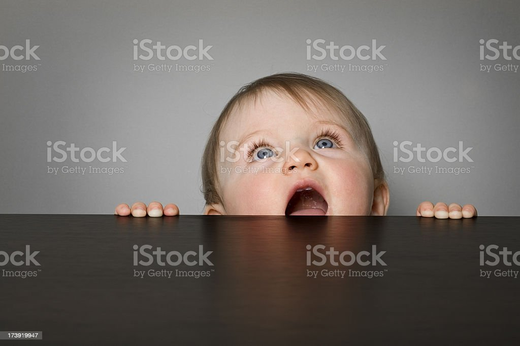 Baby girl peeking over a table royalty-free stock photo