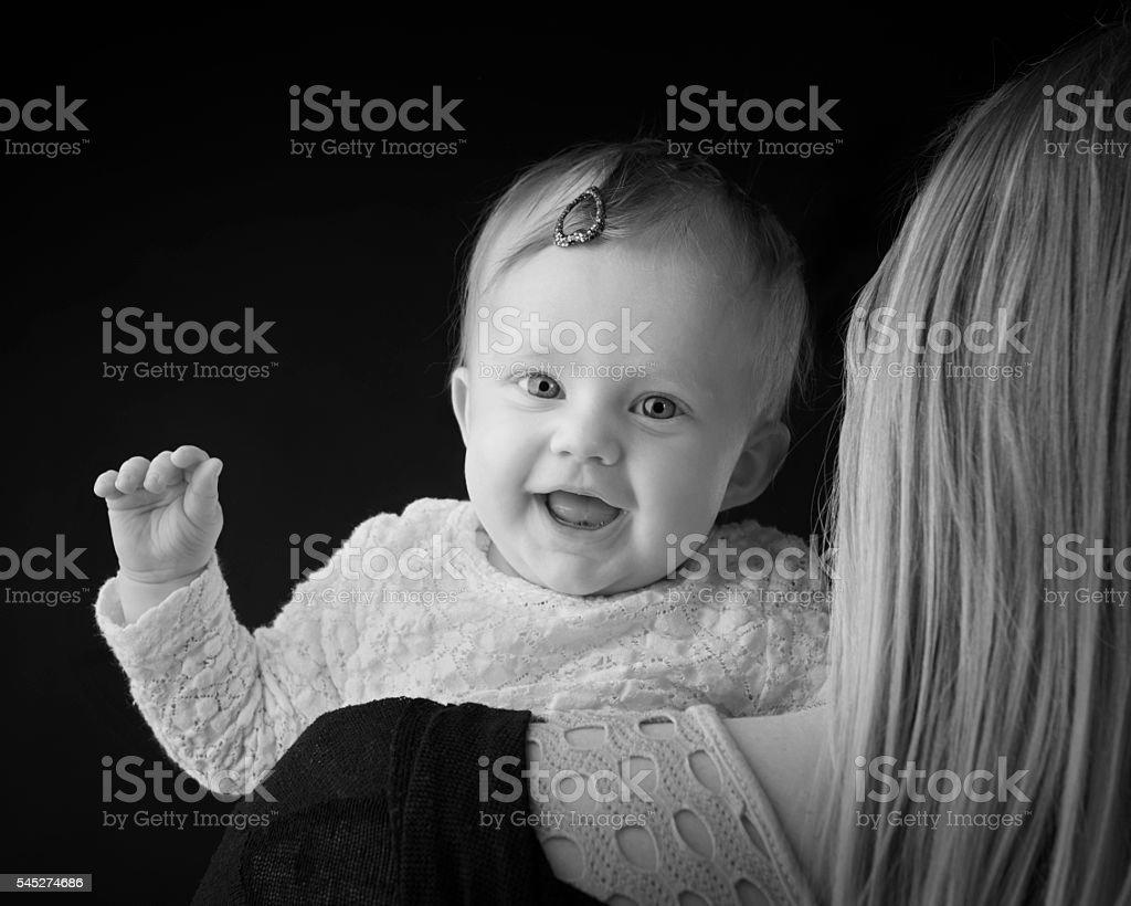 Baby girl peeking over mothers shoulder stock photo