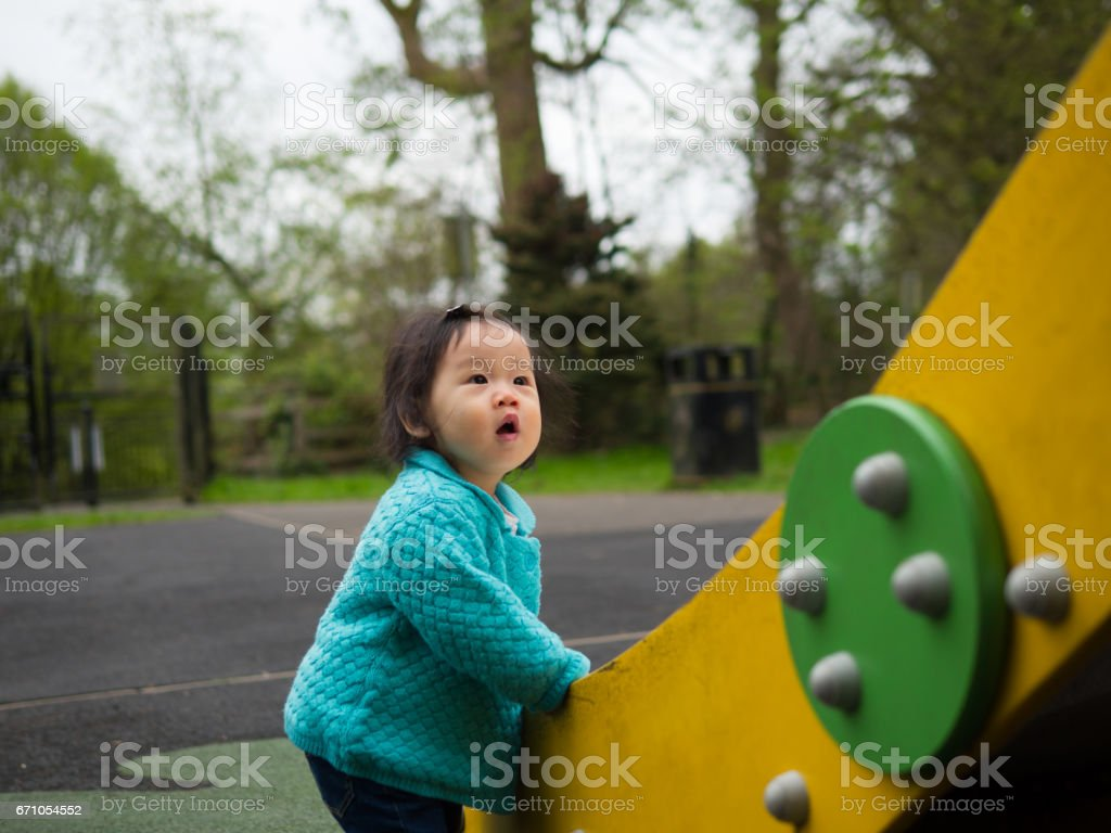 baby girl playing slide in the playground stock photo