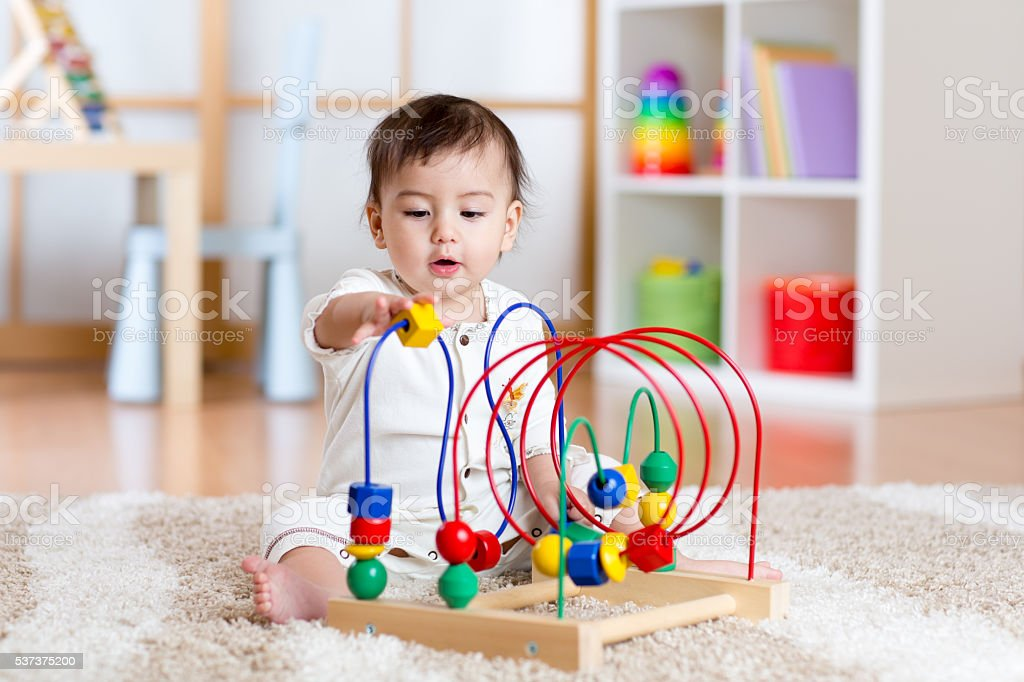 baby girl playing with educational toy in nursery stock photo