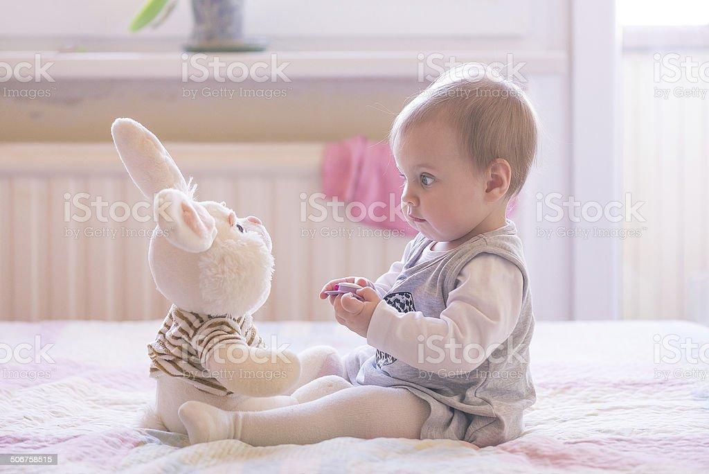 Baby girl playing with plush rabbit stock photo