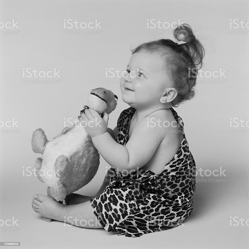 Baby girl playing with toy dinosaur, smiling royalty-free stock photo