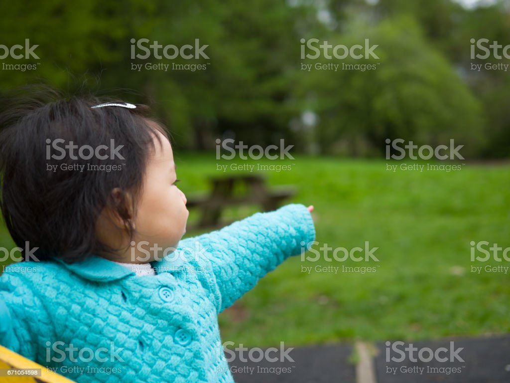 baby girl pointing distant place stock photo