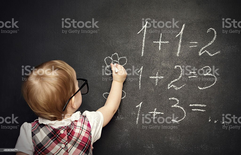 baby girl pupil draws a chalk on blackboard royalty-free stock photo