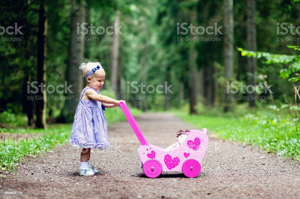 Baby girl pushes her wooden doll buggy in the forest stock photo