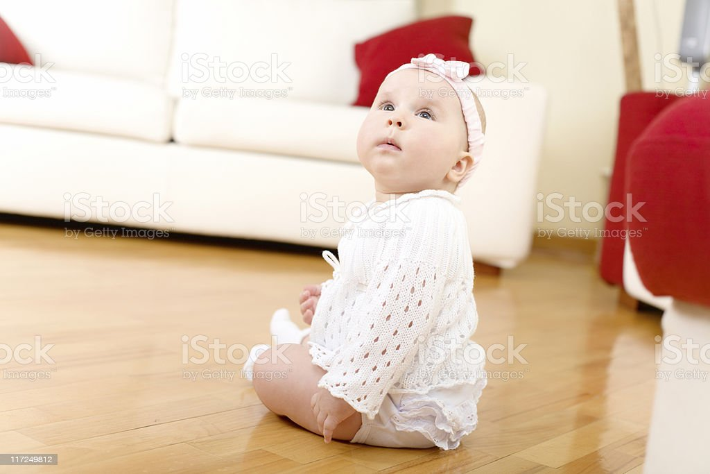 Baby girl seated on a hardwood floor royalty-free stock photo