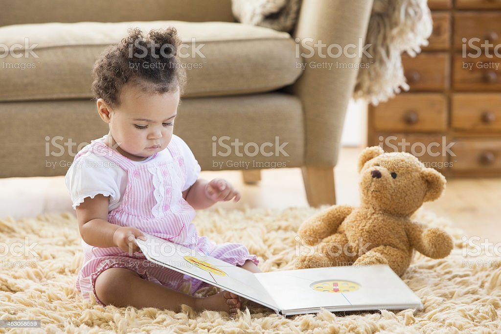 Baby Girl Sits With A Book stock photo