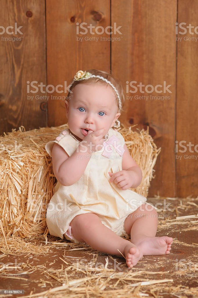 Baby Girl Sitting Against a Straw Bale stock photo