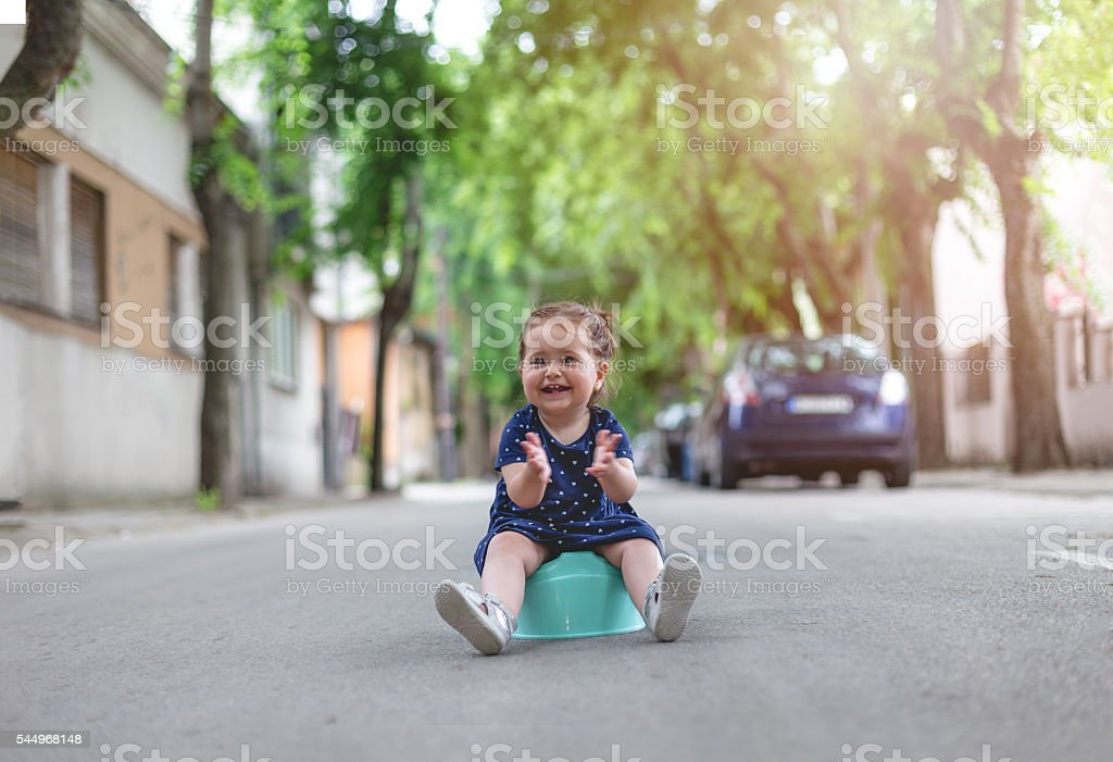 baby girl sitting on a potty outdoors and clapping stock photo