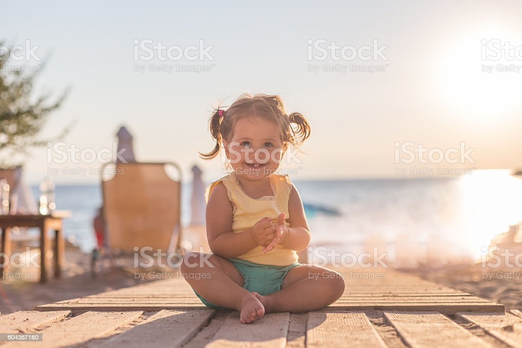 baby girl sitting on a wooden path on a beach stock photo