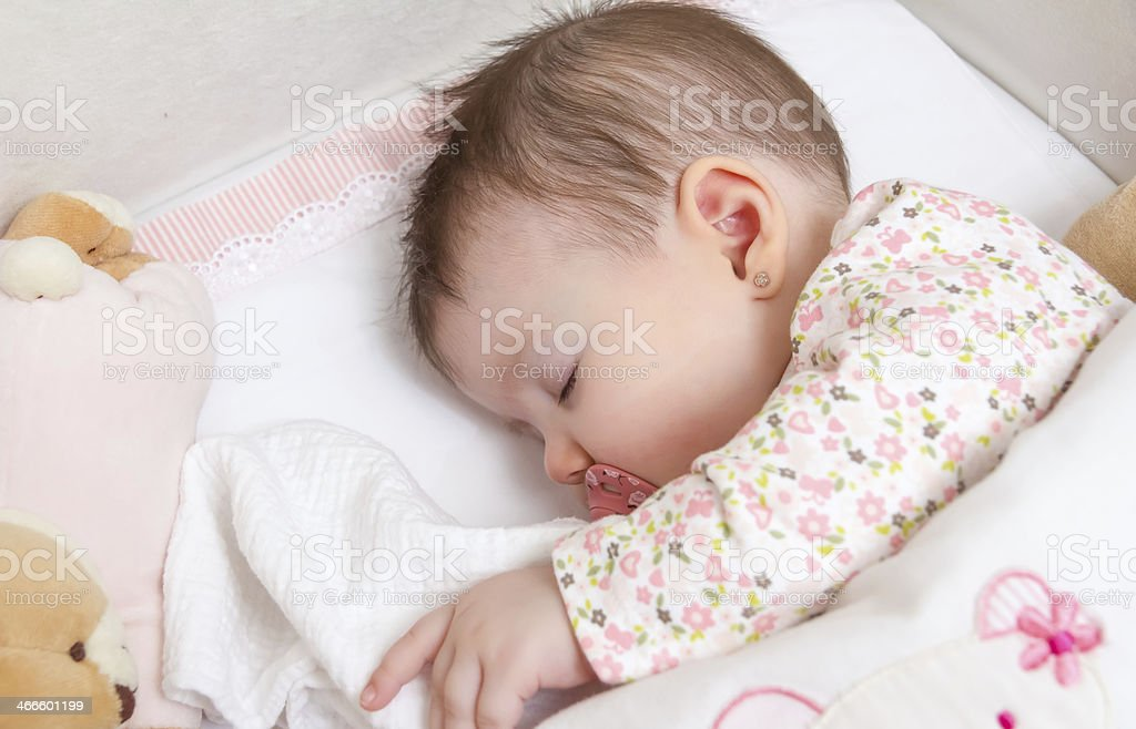 Baby girl sleeping in a cot with pacifier and toy stock photo