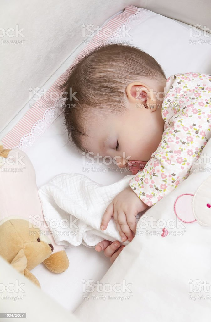 Baby girl sleeping in a cot with stuffed animal and pacifier stock photo